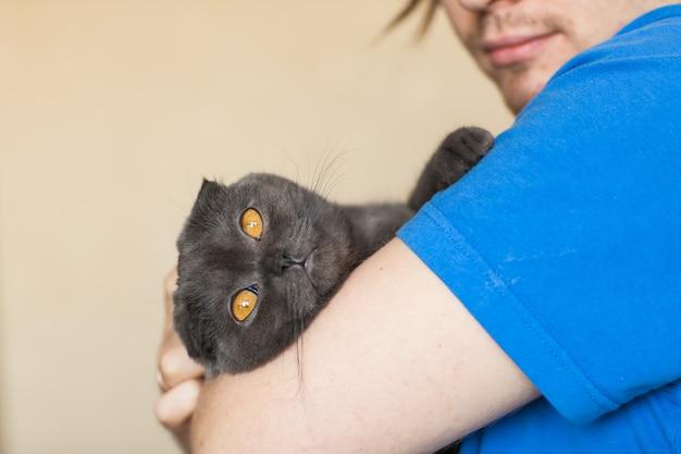 Eigenaar en huisdierenconcept - jonge mens die een grijze schotse vouwenkat houden