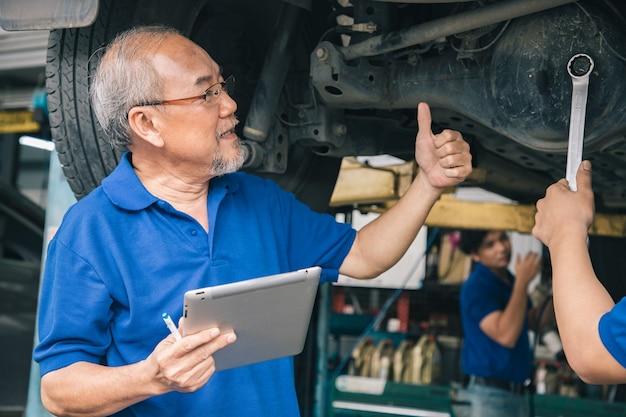 Eigenaar en servicepersoneel gebruikte tablet voor reparatie en vaste machine in een garage.