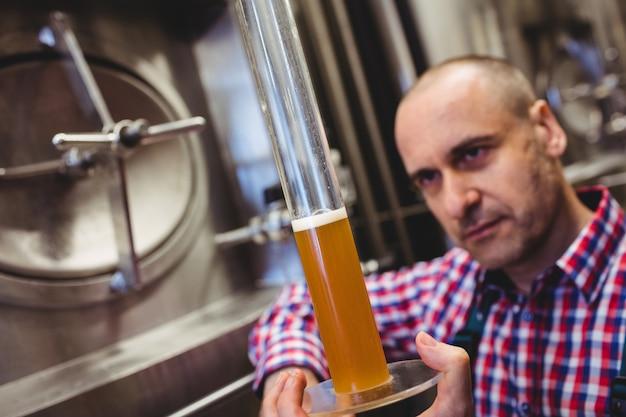 Eigenaar inspecteren bier in glazen buis