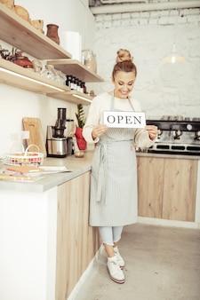 Eigenaar opstarten. gelukkige mooie coffeeshopeigenaar die lacht vanwege de opening van haar nieuwe plek.