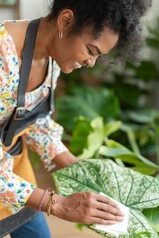 Eigenaar van een plantenwinkel die het blad van een potplant schoonmaakt