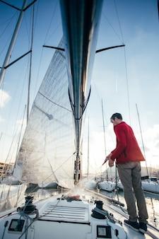 Eigenaar van zeilboot of zeiler gebruikt een slang om zout water van het yachr-dek af te spoelen wanneer hij bij zonsondergang in de jachthaven is aangemeerd of geparkeerd