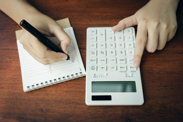 Eigenaar zittend op de jaarlijkse belastingberekening armbanden uit omzet om de belasting te verminderen.