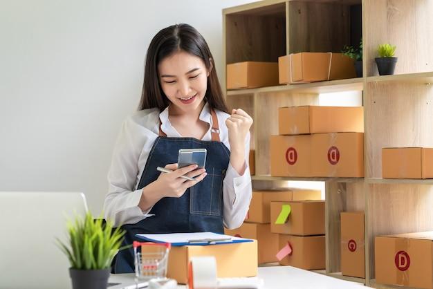 Eigenaars van kleine bedrijven die een schort dragen, verkopen succesvol online met behulp van een thuis geplaatste smartphonepakketdoos.