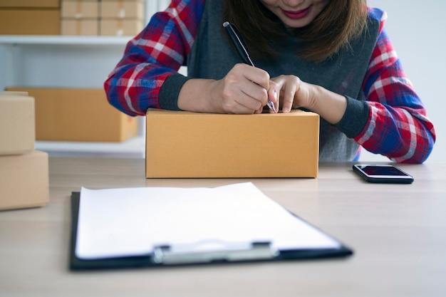 Eigenaren van kleine bedrijven schrijven namen om zich voor te bereiden op het bezorgen van pakketten aan klanten. kleine bedrijven die online verkopen en online producten bestellen