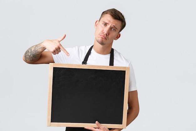 Eigenaren van kleine winkels, café- en restaurantmedewerkersconcept. boos sombere en verontruste verkoper wijzende vinger naar krijtbord zonder tekenen, staande witte achtergrond teleurgesteld.