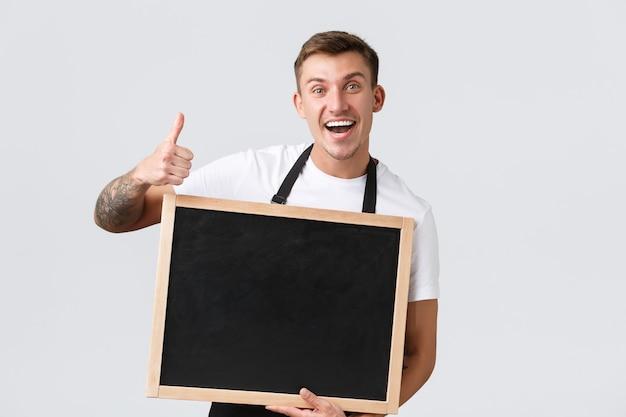 Eigenaren van kleine winkels, café- en restaurantmedewerkersconcept. enthousiaste vriendelijke en vrolijke verkoper in zwarte schort, duim omhoog en leeg bord voor je kopieerruimteteken, witte achtergrond