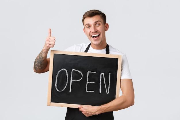 Eigenaren van kleine winkels, café- en restaurantmedewerkersconcept. vriendelijke vrolijke lachende barista, ober of verkoper met open bord en duim omhoog, uitnodigend om de winkel te bezoeken, witte achtergrond