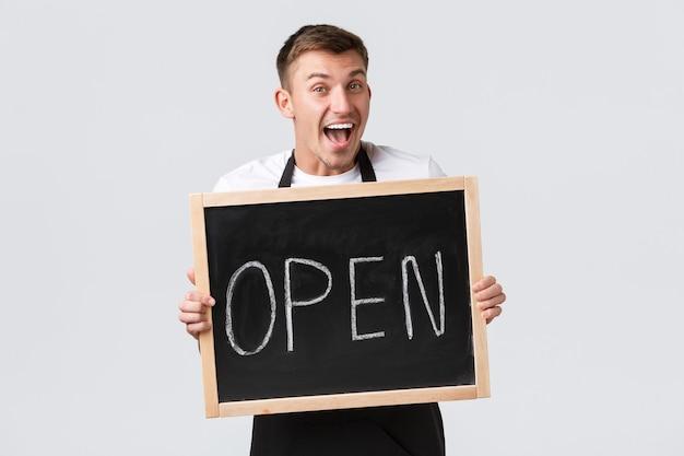 Eigenaren van kleine winkels, café- en restaurantmedewerkersconcept. vrolijk lachende barista die gasten begroet, verkoper die laat zien dat we een open teken zijn en vrolijk grijnzend, witte achtergrond