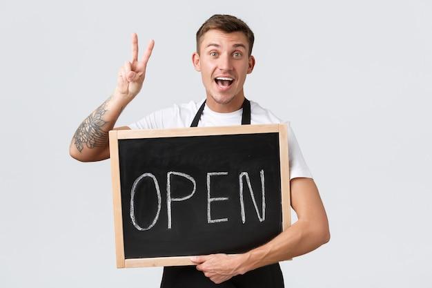 Eigenaren van kleine winkels, café- en restaurantmedewerkersconcept. vrolijke knappe ober, verkoper in zwarte schort, vredesteken tonend, gasten begroeten met open teken