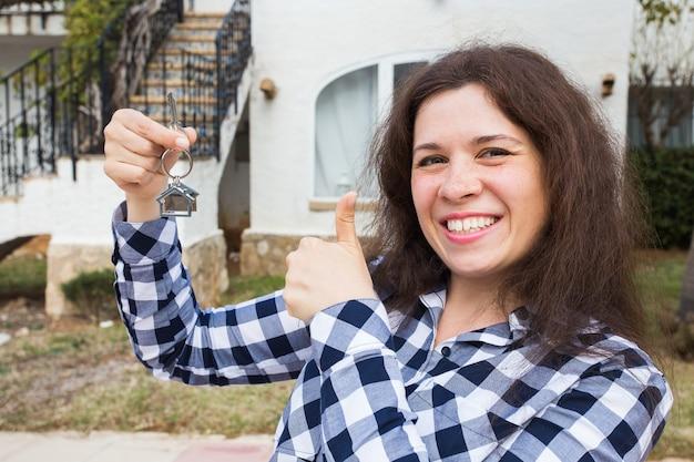 Eigendom, onroerend goed, aankoop en huurconcept - vrouw met sleutels die zich buiten nieuw huis bevinden.
