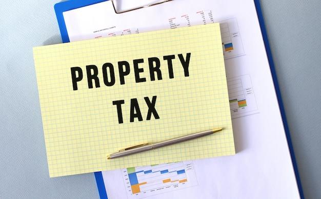 Eigendomsbelasting tekst geschreven op kladblok met potlood. kladblok op een map met diagrammen. financieel concept.