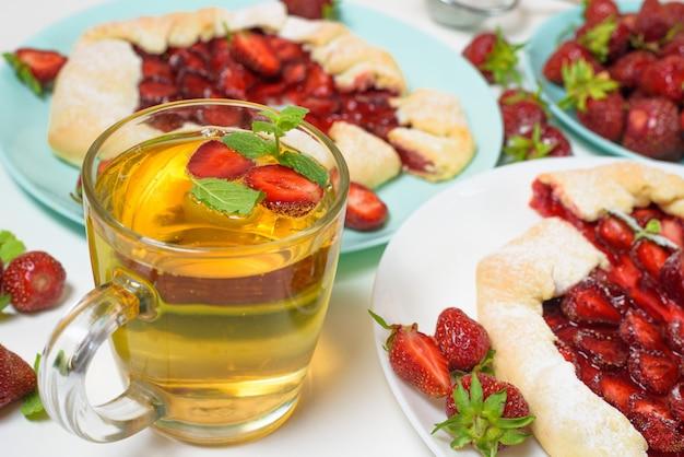 Eigengemaakt aardbeikoekje met verse rijpe aardbeien op blauwe en witte platen met thee op een licht