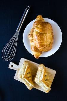 Eigengemaakt broden of broodje op houten achtergrond, croissantrookwolk en pastei, ontbijtvoedsel