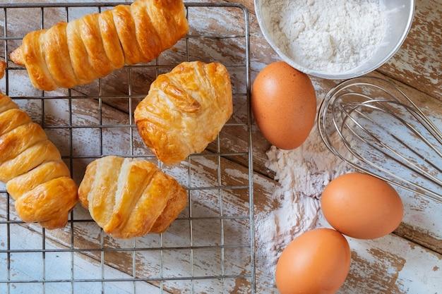 Eigengemaakt brood met ei en kom bloem op houten achtergrond