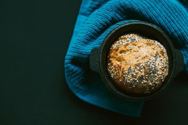 Eigengemaakt brood met zaden in de zwarte container op textiel tegen zwarte achtergrond