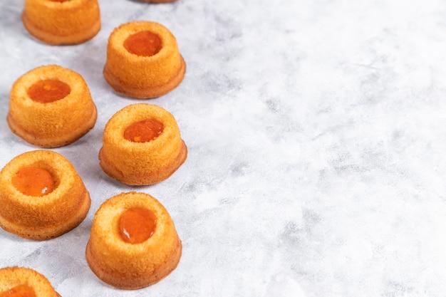 Eigengemaakt de thumbprintkoekje van de abrikozenjam dat op marmeren achtergrond wordt geplaatst.