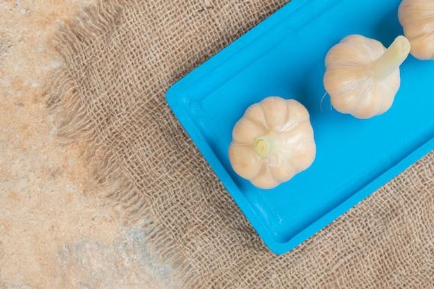 Eigengemaakt gefermenteerd knoflook op blauw bord.