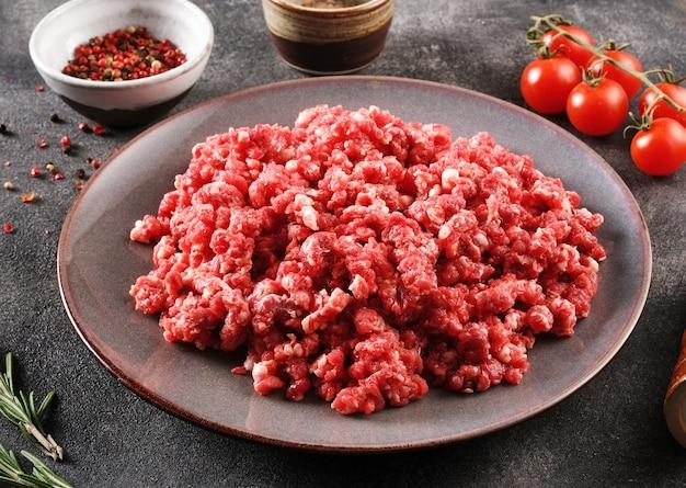 Eigengemaakt gehakt in een grijze kom over donkere achtergrond of steenachtergrond met ingrediënten voor het maken.