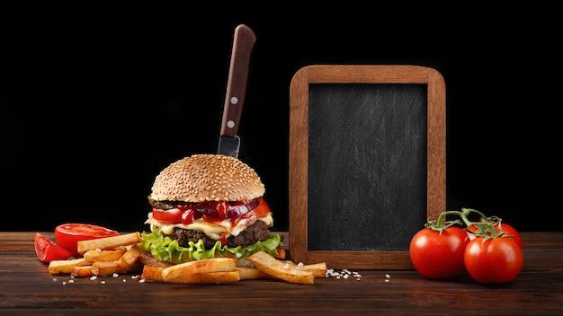 Eigengemaakt hamburgerclose-up met rundvlees, tomaat, sla, kaas, frieten en schoolbord op hout