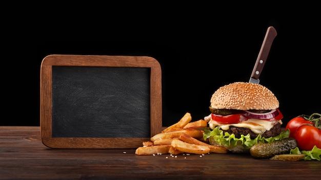 Eigengemaakt hamburgerclose-up met rundvlees, tomaat, sla, kaas, frieten en schoolbord op houten lijst