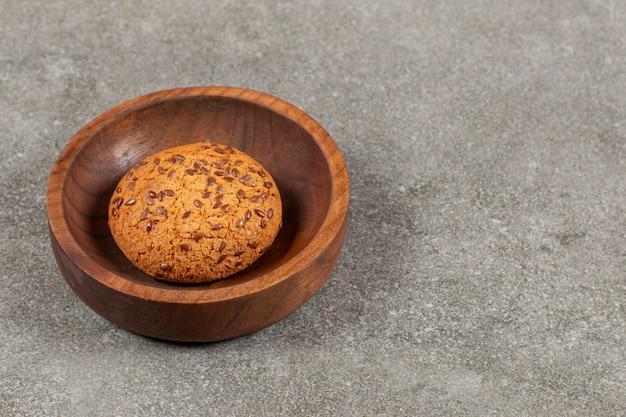 Eigengemaakt koekje in houten kom over grijs.
