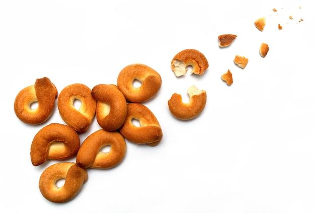 Eigengemaakt ongezuurd broodje dat op witte achtergrond wordt geïsoleerd. traject of vlucht van kapotte onderdelen en kruimels bovenaanzicht