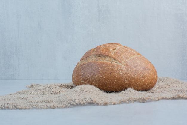 Eigengemaakt roggebrood op jute op marmeren achtergrond. hoge kwaliteit foto
