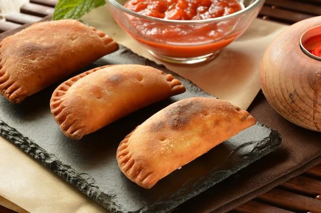 Eigengemaakt tonijnpasteitje met tomatensaus op houten lijst