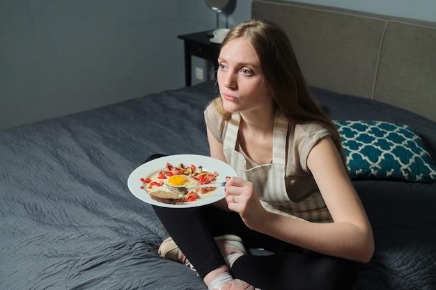 Eigengemaakt voedsel op plaat in handen van jonge vrouw