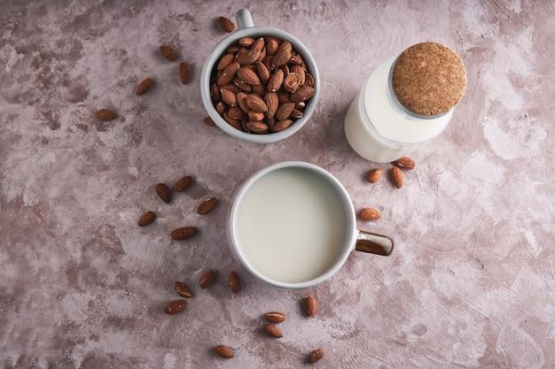 Eigengemaakte amandelmelk in een kop en een fles, amandelpitten op rustieke oppervlakte. alternatief eten en drinken. bovenaanzicht kopieer ruimte