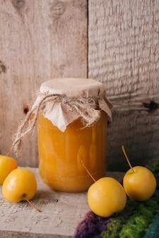 Eigengemaakte appeljam of saus, met gele appelen, houten rustieke achtergrond.
