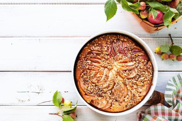 Eigengemaakte appeltaart en ingrediënten op een witte houten oppervlakte