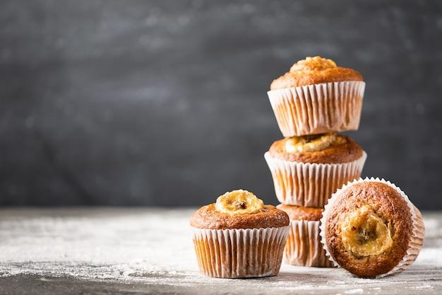 Eigengemaakte banaanmuffins in een stapel op een grijze achtergrond. gezond vegan dessert.