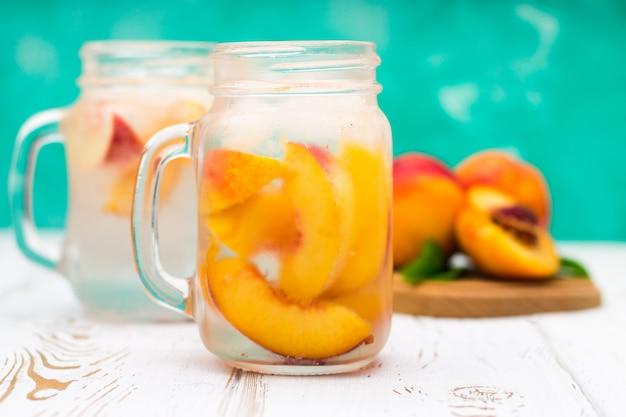 Eigengemaakte bevroren limonade met rijpe perziken. verse perzikijsthee in een metselaarkruik.