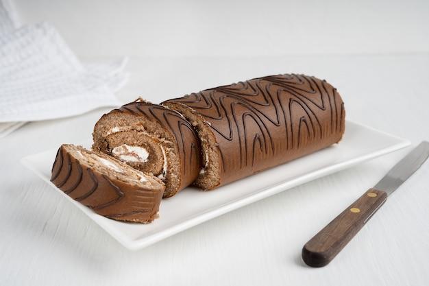 Eigengemaakte bruine biscuitgebakcake of rollade met roomvulling die op plaat met keukenmes wordt gesneden