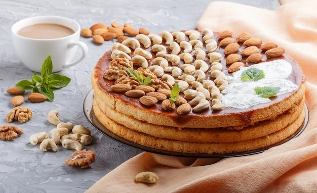 Eigengemaakte cake met karamelroom en noten met kop van koffie op grijs beton