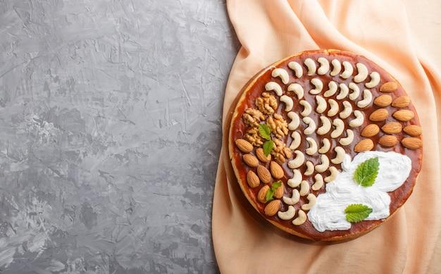 Eigengemaakte cake met karamelroom en noten op een grijze concrete, hoogste mening.