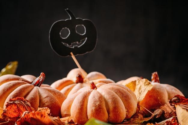Eigengemaakte cakes in de vorm van halloween-pompoen met de herfstbladeren