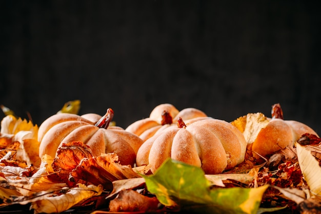 Eigengemaakte cakes in de vorm van pompoen en de herfstbladeren op dark met exemplaarruimte. koken voor halloween