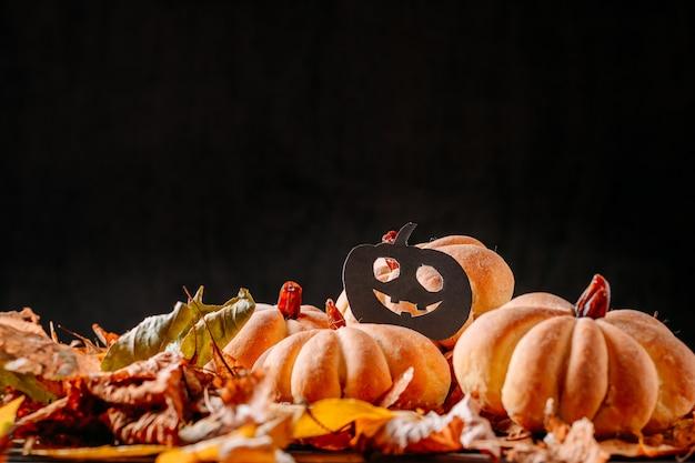 Eigengemaakte cakes in vorm van halloween-pompoen met de herfstbladeren