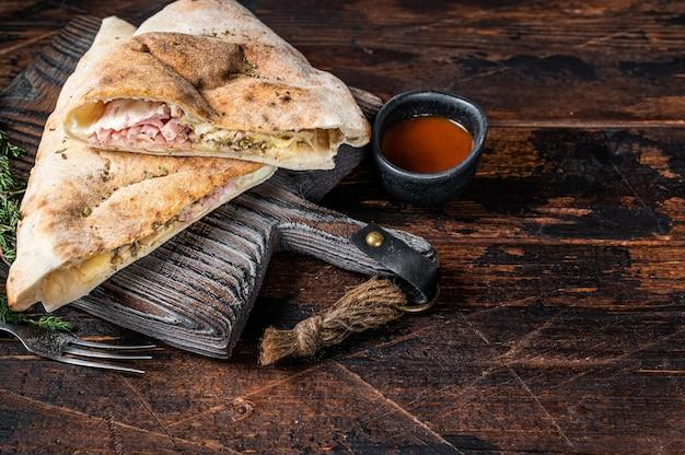 Eigengemaakte calzone gesloten pizza met ham en kaas op een houten bord