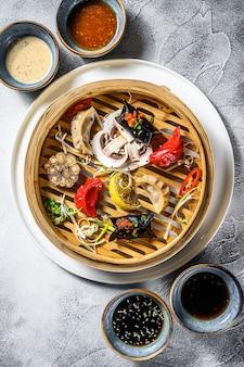 Eigengemaakte chinese en koreaanse dumplings die op de traditionele bamboestoomboot worden gediend
