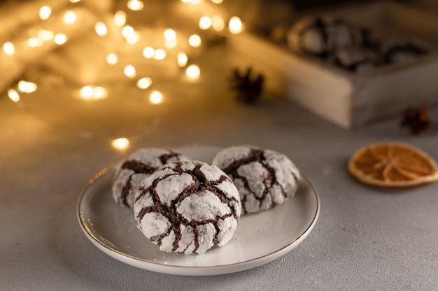 Eigengemaakte chocolade gerimpelde koekjes in witte plaat tegen vage kerstmislichten