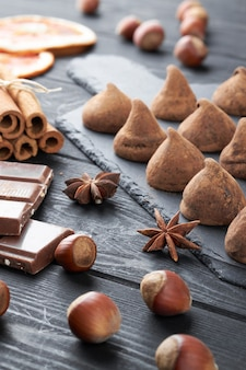 Eigengemaakte chocoladetruffels en geassorteerde chocolade met noten en andere kruiden op rustieke oude keukentafel.