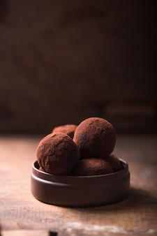 Eigengemaakte chocoladetruffels op de houten mening van de lijstclose-up. lekker vegetarisch snoep of balletjes met rauw cacaopoeder