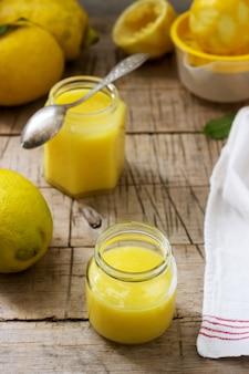 Eigengemaakte citroengestremde melk met kruiken en citroenen op houten achtergrond