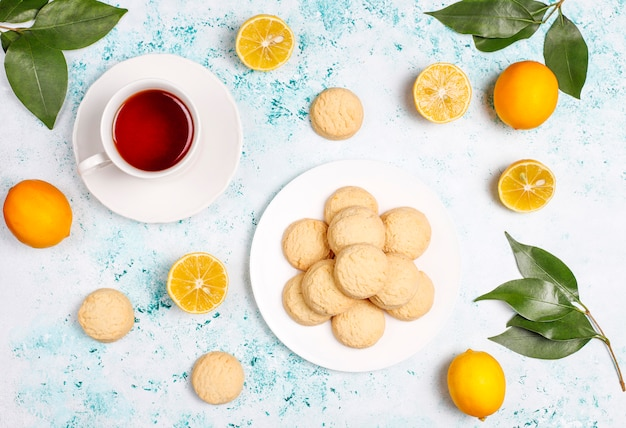 Eigengemaakte citroenkoekjes met citroenen op lichte oppervlakte
