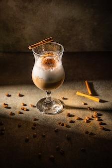 Eigengemaakte dalgona-koffie op donkere achtergrond. naast koffiebonen en kaneelstokjes.