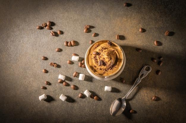 Eigengemaakte dalgona-koffie op donkere achtergrond. naast koffiebonen en marshmallows.